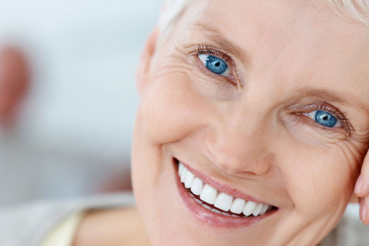 woman smiling after a single tooth dental implant procedure